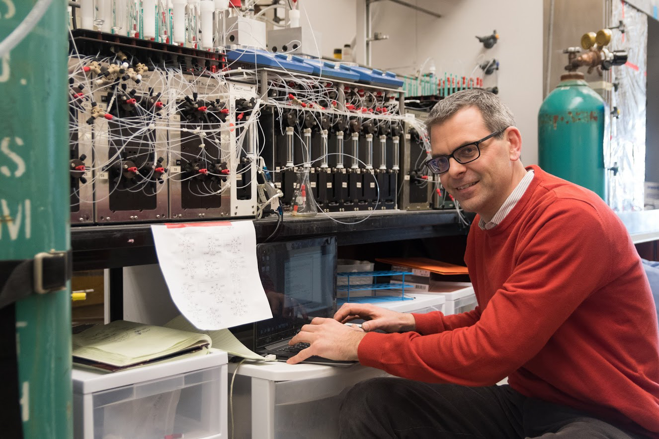 Professor Martin Burton poses  with his molecular making machine at the Roger Adams Laboratory.