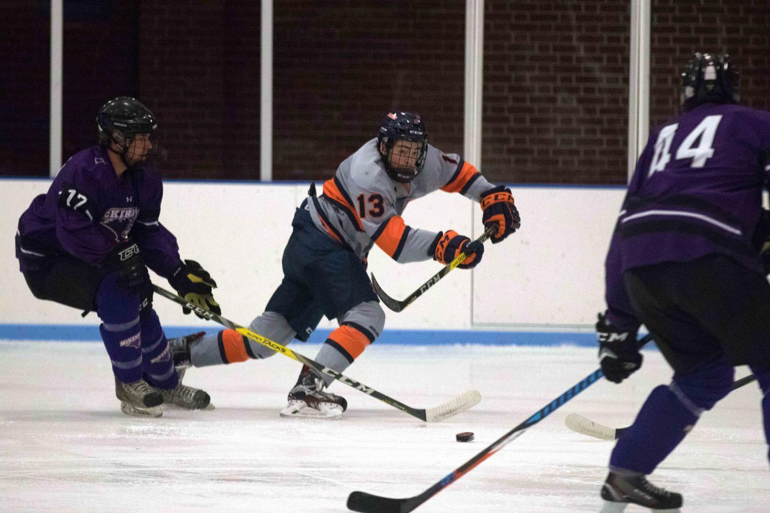 James McGing (13) passes the puck past McKendree's players to his line mate across the ice at the Ice Arena on Friday, Oct. 13th. Illinois beat McKendree 4-2.