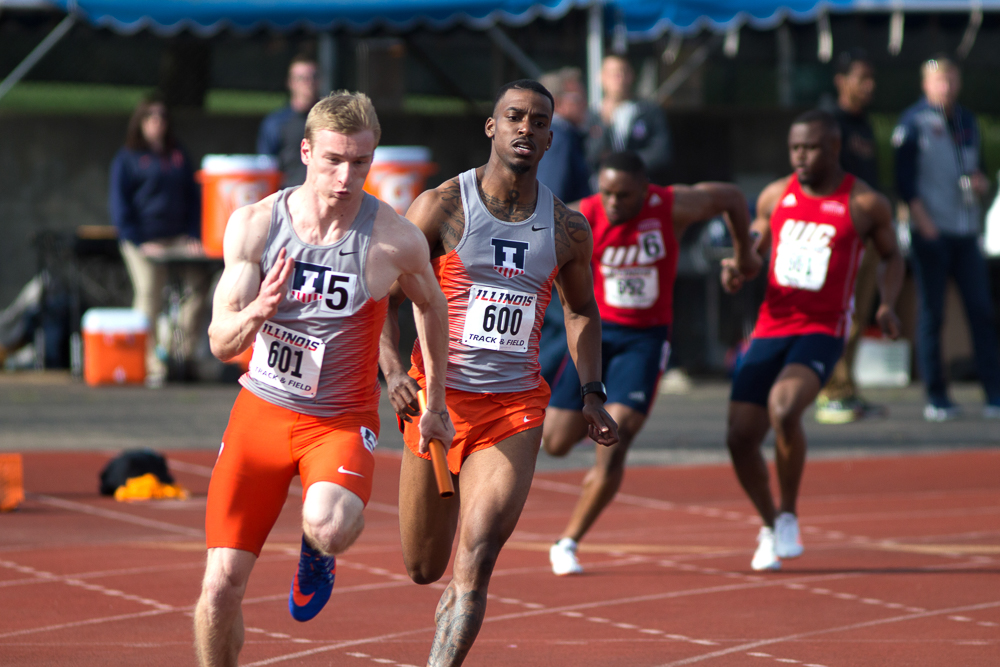 Mo Maat sprints up behind Devin Quinn to hand off the baton for the last dash in the 4x100 Meter Relay at Illinois Twilight at the Illinois Track Field on April 22. Quinn completed his senior campaign after multiple successes, taking away records like the fastest men's 100-meter in the Big Ten conference and Illinois history.
