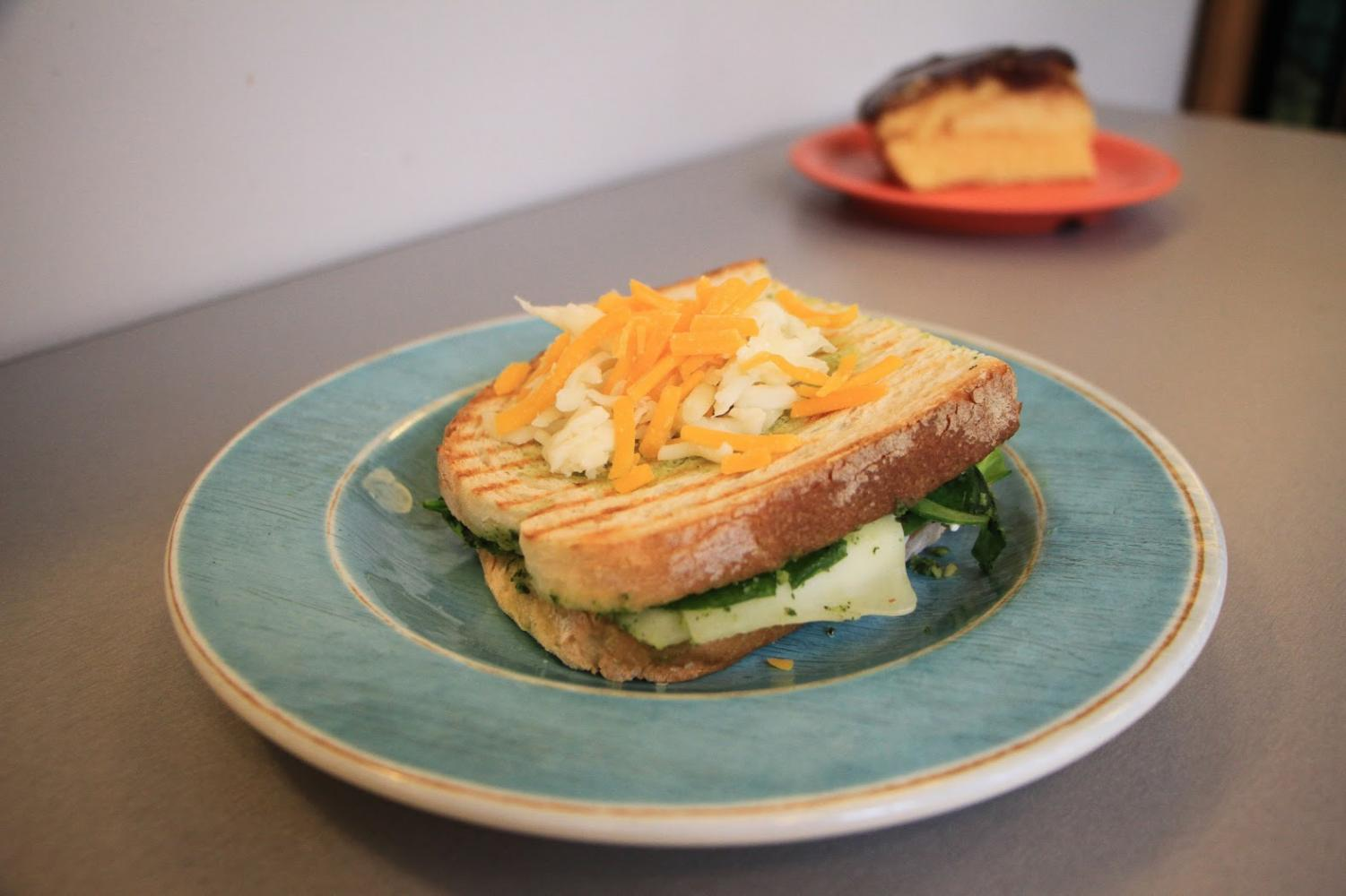 It's time to take your sandwich game up a notch! Mixing up your food and trying new combinations is a good way to change the monotony of your dining hall experience. Here is a caprese sandwich that is topped with shredded cheddar and mozzarella. In the background a Boston cream pie dessert!