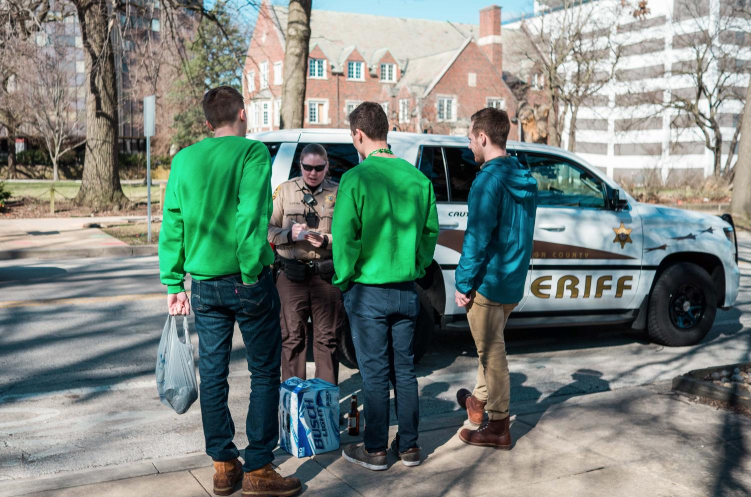 sabrina yan The Daily Illini A police officer issues tickets to three people on Fifth Street in the morning on Unofficial St. Patrick's Day, March 3, 2017. The mayors of Champaign and Urbana are placing further restrictions on the holiday this year.
