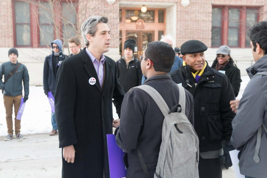 Illinois Democratic gubernatorial candidate Daniel Biss fastens an I love GEO pin as he greets Rahul Raju, student in Engineering, at the Daniel Biss Rally on the Main Quad on Thursday. The Graduate Employees Organization announced today that it will begin striking on Feb. 26.