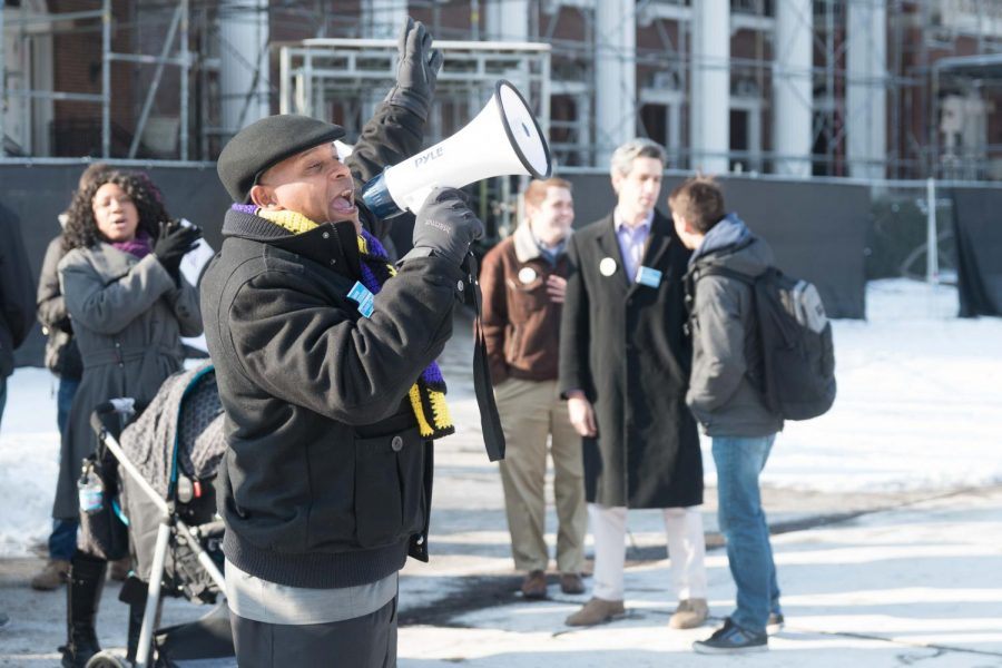 Candidate for Champaign county clerk Aaron Ammons uses a megaphone to invite passing students to meet with gubernatorial candidate Daniel Biss on Thursday.