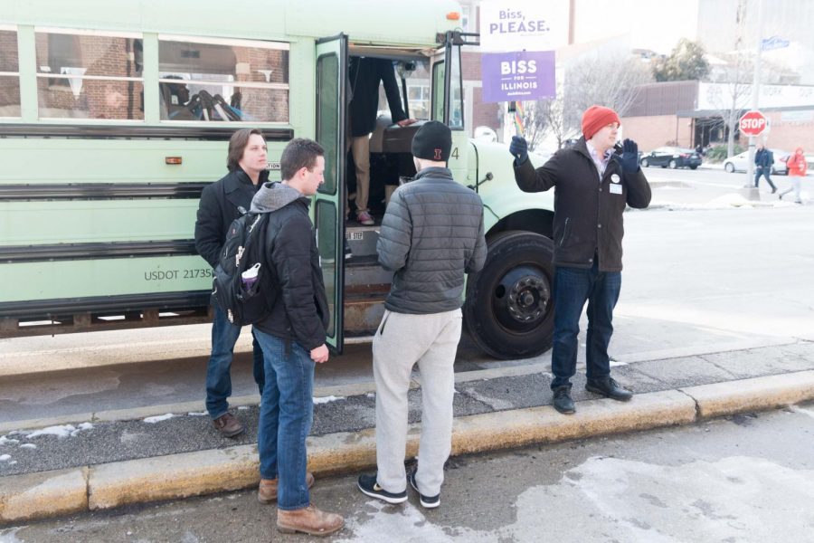 Students gather to board a bus taking them to participate in early voting following the Daniel Biss Rally on Thursday.