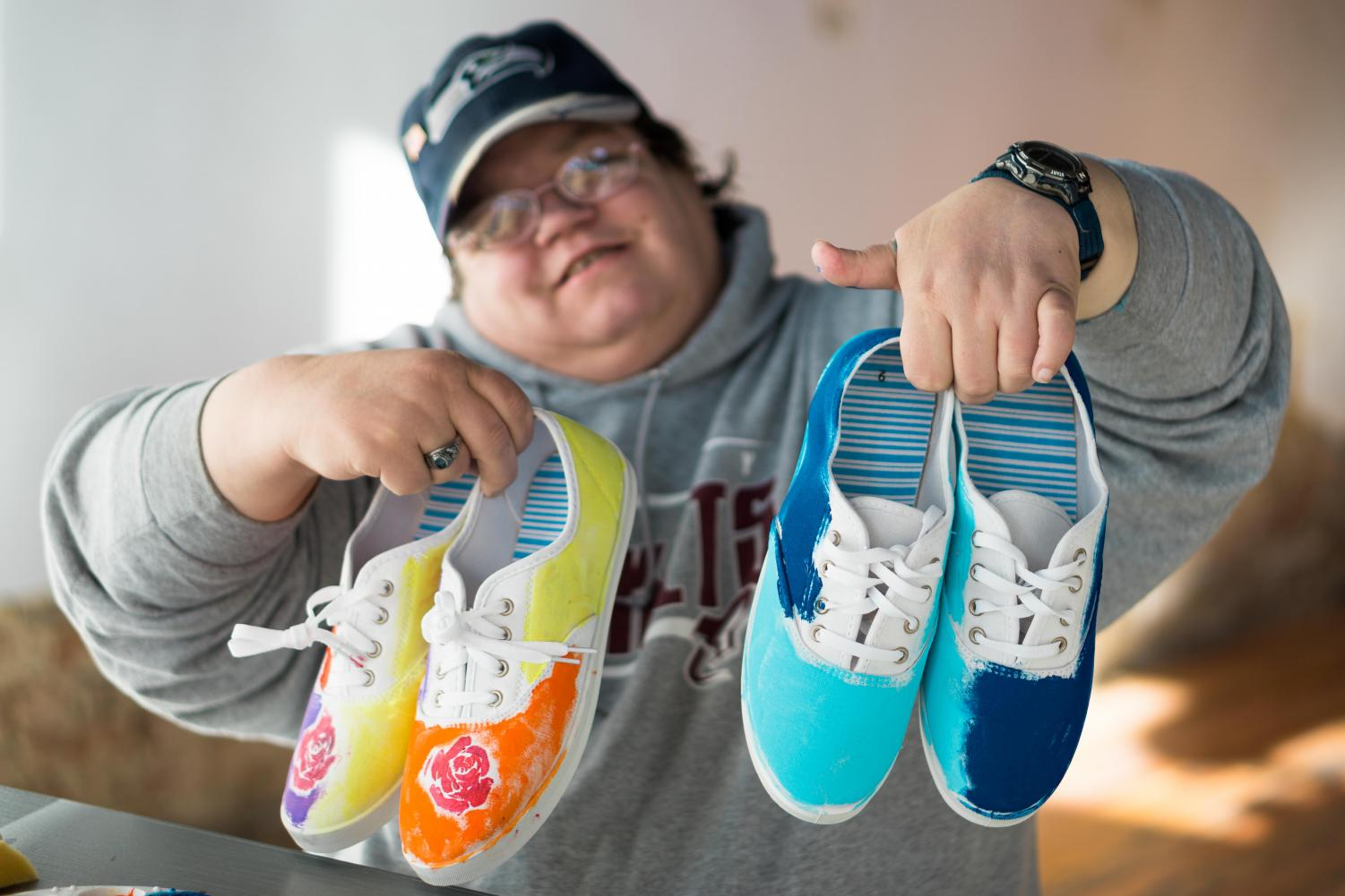 A Creative Souls employee holds up shoes they painted. The local shoe company, which specializes in hiring people with disabilites, is attempting to raise $50,000 to expand hiring.