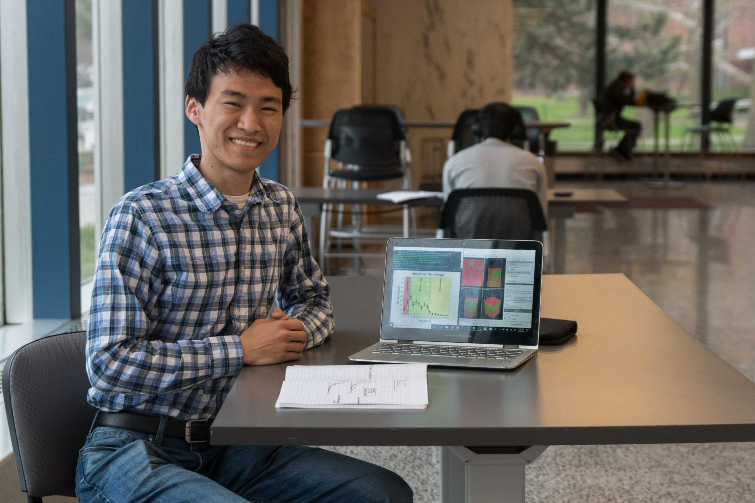 Goldwater scholarship recipient Michael Toriyama poses with his research in Loomis Laboratory of Physics.  In his research, Toriyama conducts simulations of ion radiation in semiconductors.