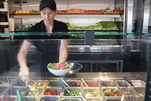 Jeni McLaughlin, assistant manager of CoreLife Eatery, puts together a Mediterranean green bowl, a customer favorite at CoreLife. Its menu provides students with healthy alternatives that are free of GMOs, trans fats, artificial colors, sweeteners, antibiotics, hormones and other artificial additives.