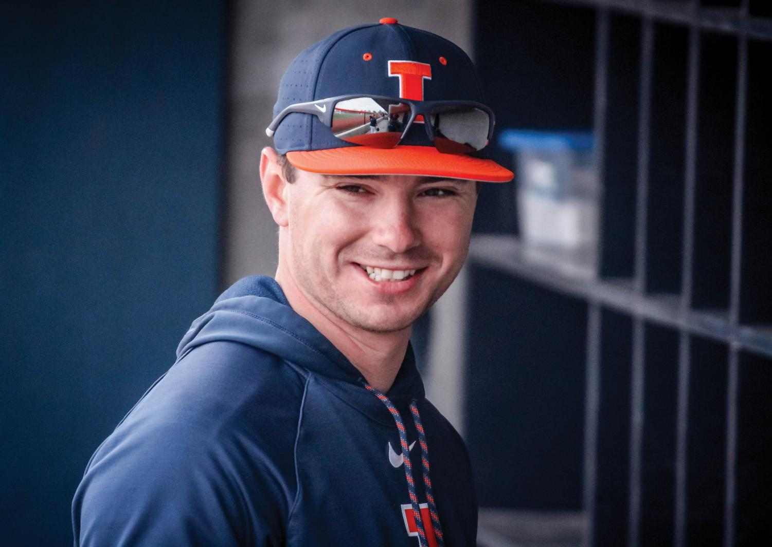 Assistant coach Casey Fletcher smiles in the dugout. Fletcher played at Illinois for two seasons before a brief stint with the Frontier league.