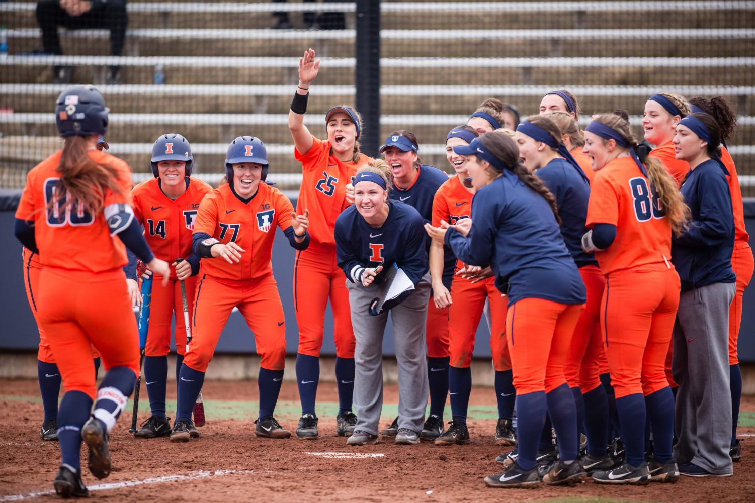 The Illini softball team celebrates at home plate after outfielder Veronica Ruelius (00) hit a home run during the game against Northwestern at Eichelberger Field on Wednesday, Mar. 28, 2018.