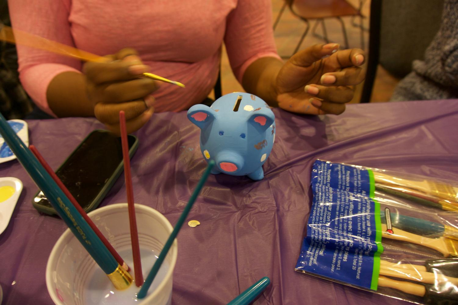 Students painting piggy banks at the Paint a Pig event.