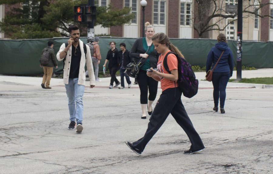 University students cross the street with phones in hand all over campus.