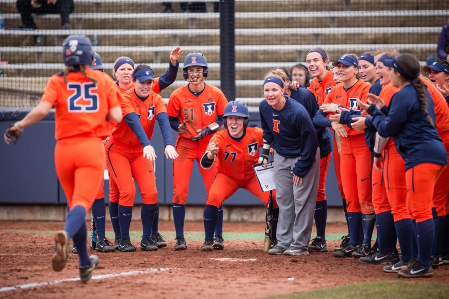 The+Illini+softball+team+celebrates+at+home+plate+after+outfielder+Carly+Thomas+%2825%29+hit+a+home+run+during+the+game+against+Northwestern+at+Eichelberger+Field+on+Wednesday%2C+Mar.+28%2C+2018.
