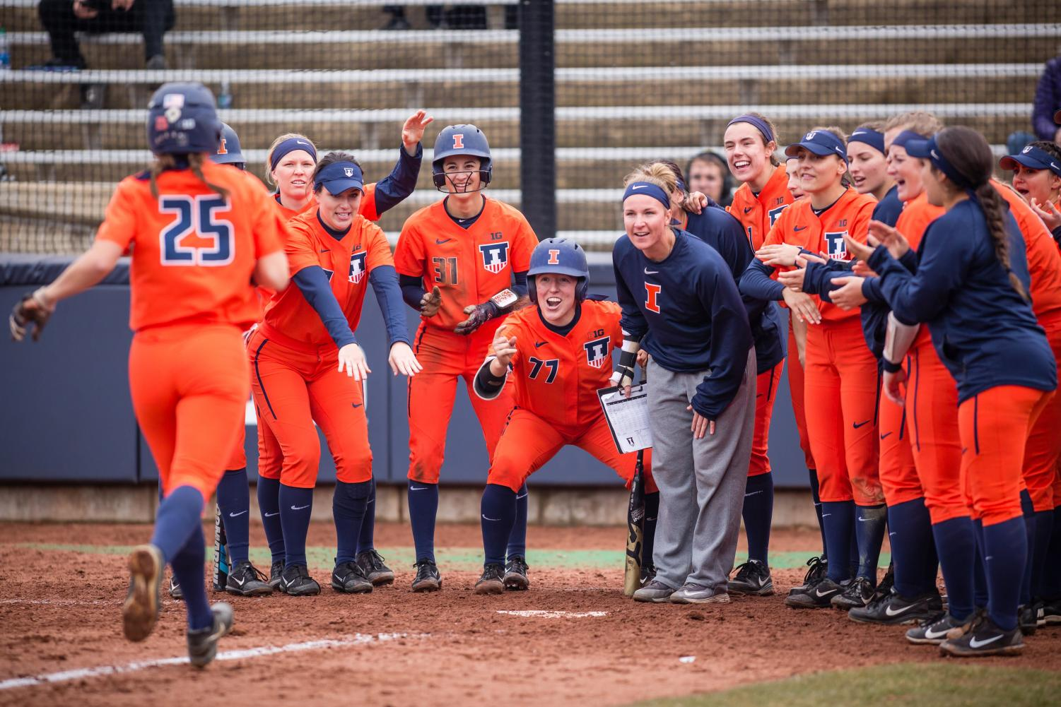 The Illini softball team celebrates at home plate after outfielder Carly Thomas (25) hit a home run during the game against Northwestern at Eichelberger Field on Wednesday, Mar. 28, 2018.