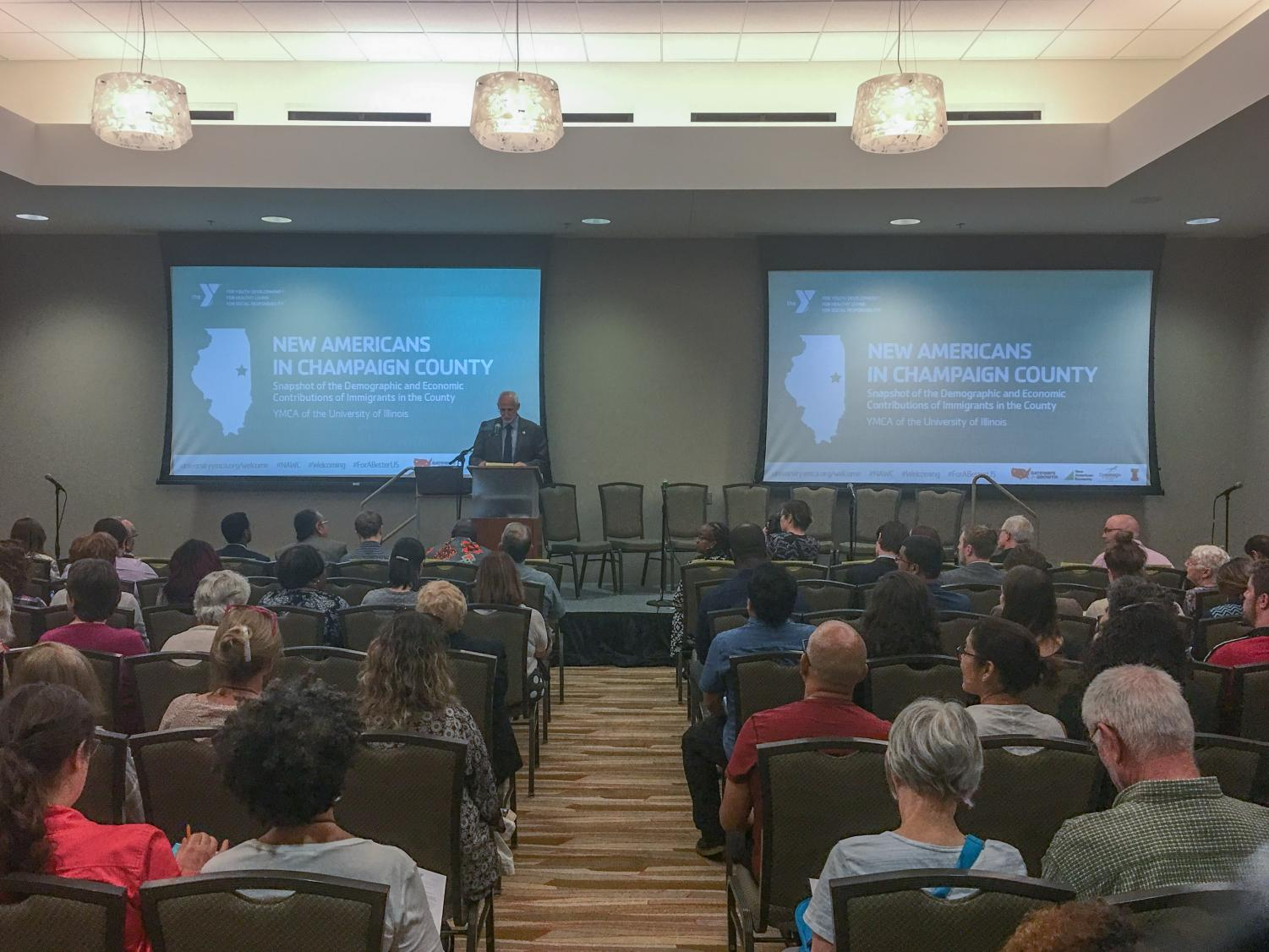 Mike Doyle, the executive director of the University YMCA, makes an opening statement at the New Americans in Champaign County community program at the I-Hotel & Conference Center on Wednesday. The program allowed community members to come together to discuss the impact of immigrants in the community.