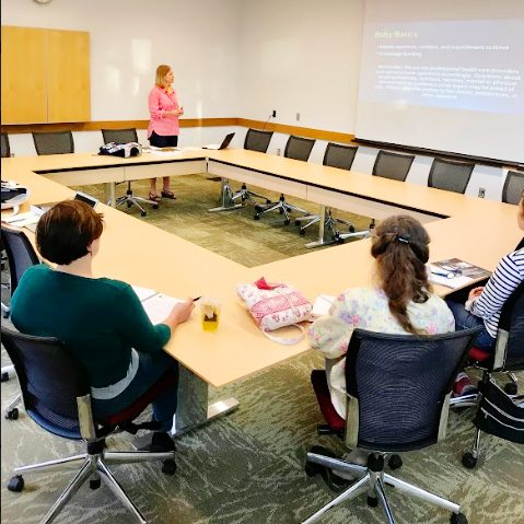 An instructor teaches volunteers for Sistering CU in the Champaign Public Library in May of 2017.