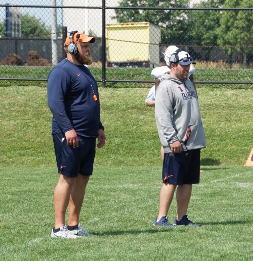 Offensive+line+coach+Luke+Butkus+%28left%29+and+defensive+line+coach+Austin+Clark+%28right%29+watch+their+players+at+Illinois+football+training+camp+on+Thursday.+Clark+is+a+new+addition+to+the+coaching+staff+and+looks+to+bring+a+higher+level+of+intensity+to+his+players.