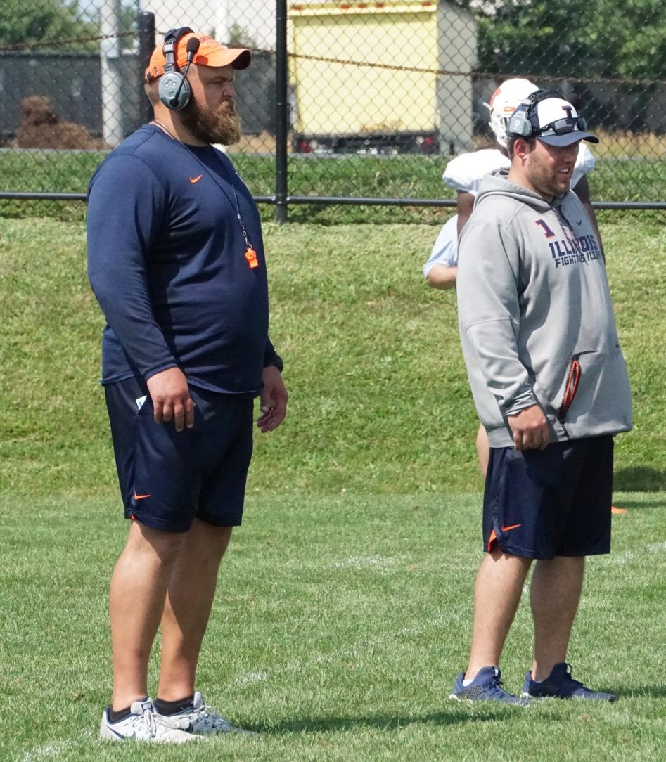 Illinois offensive line coach Luke Butkus (left) and defensive line coach Austin Clark (right) watch their players at Illinois football training camp on Aug. 9. Butkus will be leaving Illinois to join the Green Bay Packers as assistant offensive line coach.