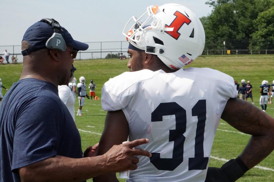 Assistant coach Gill Byrd speaks with Cameron Watkins during practice at Illinois football training camp on Wednesday. Byrd will be one coach that will have to makeup for the loss of cornerbacks coach Donnie Abraham after he left the team due to personal reasons.