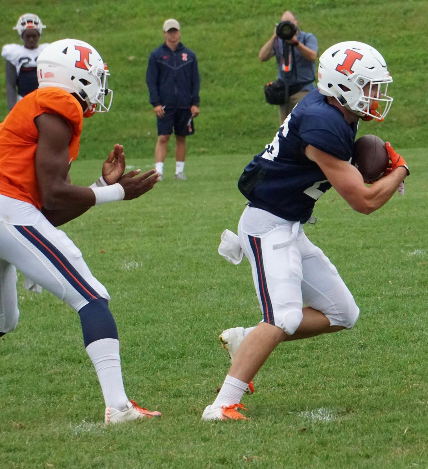 Sophomore running back Mike Epstein grabs the handoff during practice drills at Illinois football training camp on Friday. Offensive Coordinator Rod Smith is looking to utilize the team's running back depth as the season approaches.