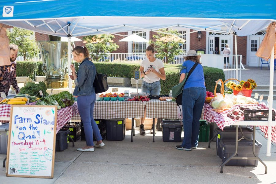 Mary Jane Oviatt and Ben Joselyn assist customers at the Thursday Farm Stand on the Quad on Aug. 23, 2018.