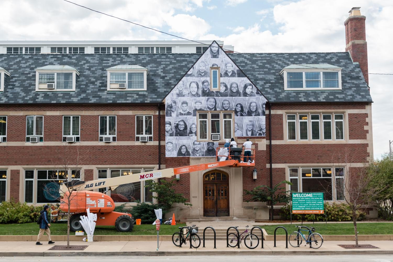 Spencer Shea, Basio Sema, and Joshua Geyer, workers for the French artist JR, put up photographs of University of Illinois students and Champaign-Urbana residents on the side of the University YMCA building at 1001 South Wright St. on Wednesday, Oct. 25, 2017. The pictures are part of an international art project called Inside Out that supports immigrants and dreamers.