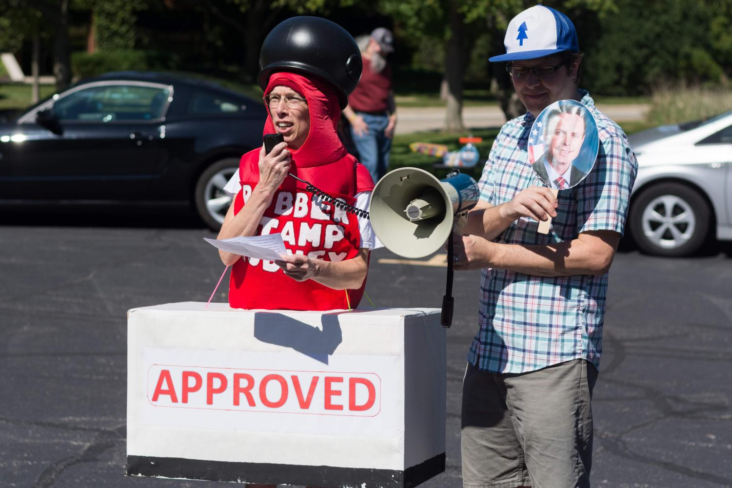 Ellen Leyerle, a Champaign resident, dressed as a rubber stamp to criticize Rep. Rodney Davis' support for President Trump's policies while she spoke at a rally outside Davis' Champaign office.
