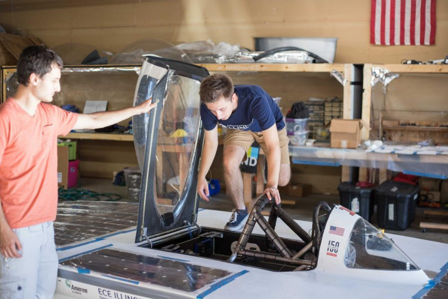 Nino Cirrincone, head of engineering for Illini Solar Car, helps teammate Kamil Czaplinski climb into the vehicle on Sunday. The 15-person team took seventh during the American Solar Challenge.