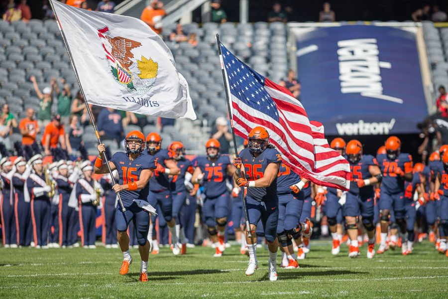 Illinois+tight+end+Austin+Roberts+%2836%29+and+quarterback+Cam+Miller+%2816%29+carry+the+American+and+Illinois+flags+onto+the+field+before+the+game+against+USF+at+Soldier+Field+on+Saturday%2C+Sept.+15%2C+2018.