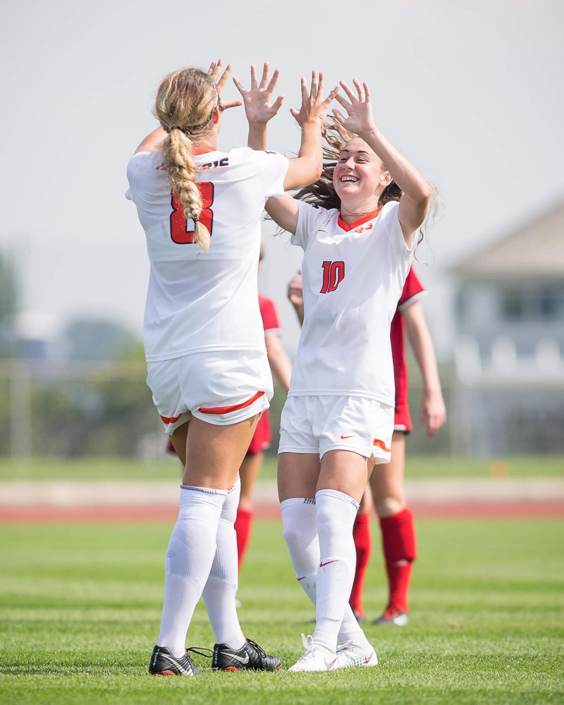Seniors Carolina Ratz (8) and Hope Breslin (10) high-five to celebrate a goal against Northern Illinois on Aug. 26. The Illini won 8-0.