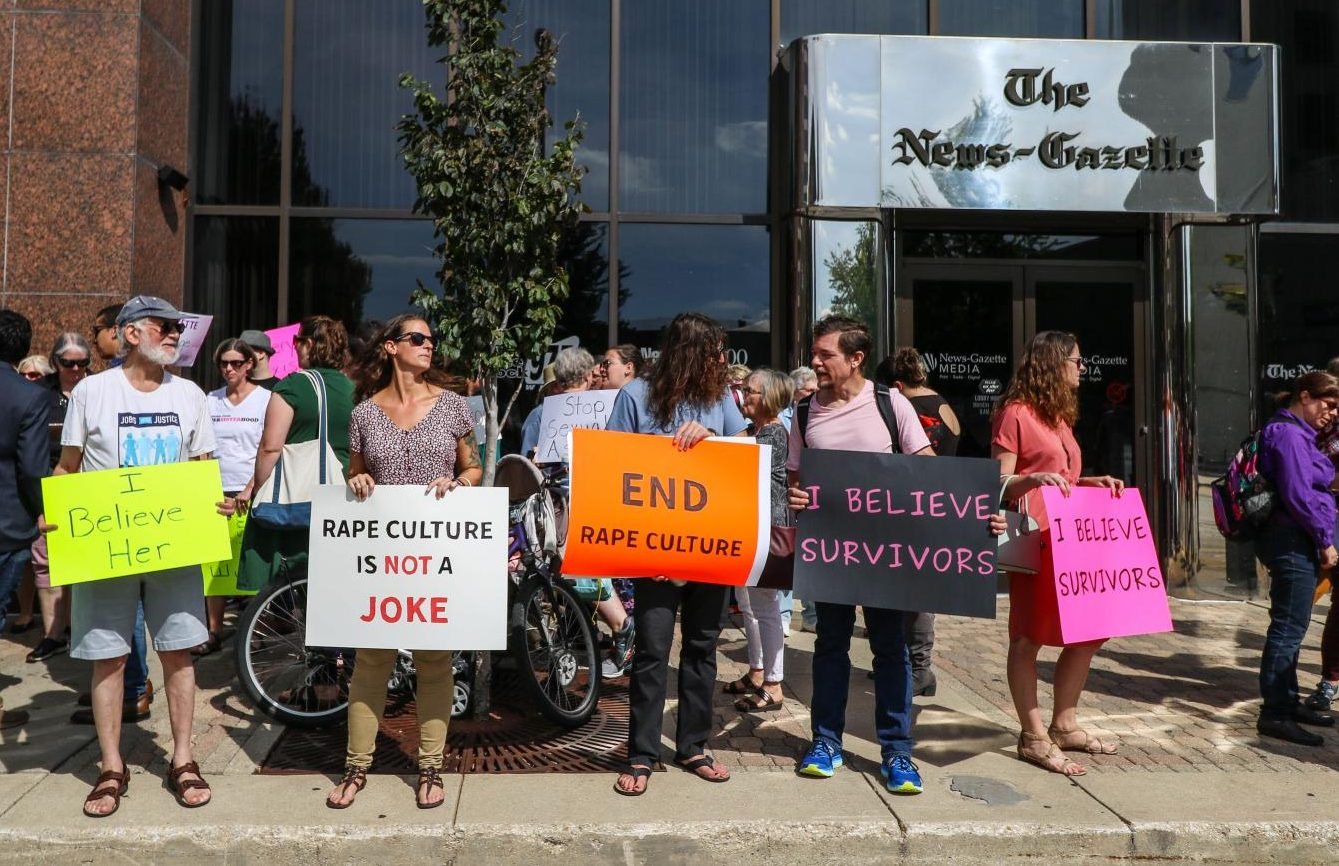Protesters stand outside The News Gazette on Oct. 1, 2018.