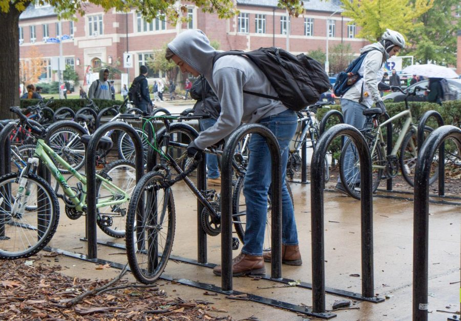 Student cyclists lock and unlock their bicycles outside the English Building. Bike thefts have decreased since last year since the UIPD introduced anti-theft bikes on campus.