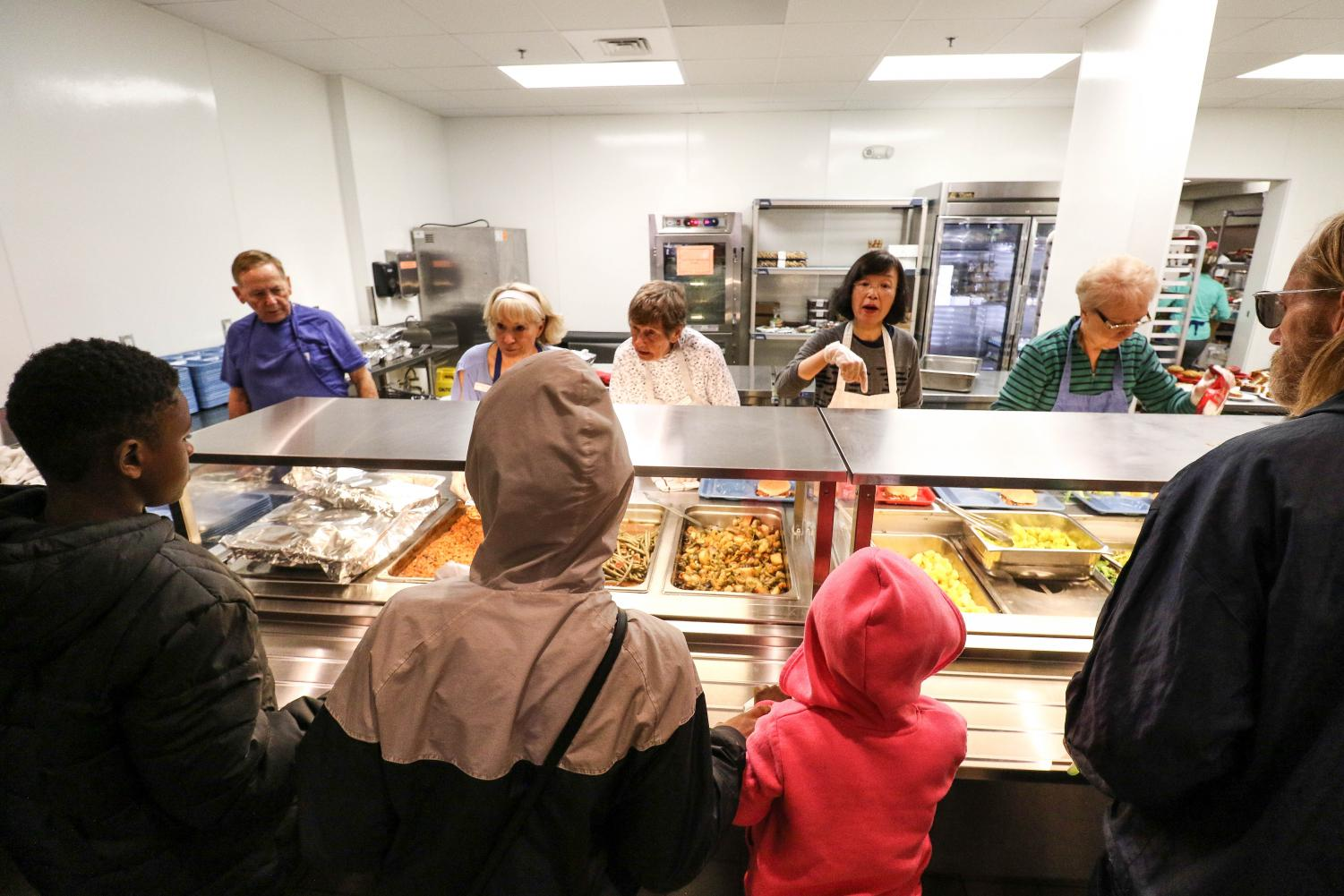 Volunteers distribute food at the Daily Bread Soup Kitchen on Wednesday.
