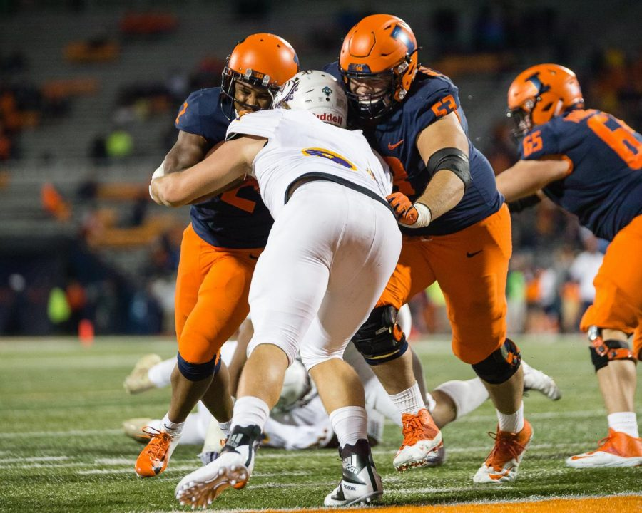 Illinois offensive lineman Nick Allegretti (right) blocks for running back Reggie Corbin (left) on his way to the end zone during the game against Western Illinois at Memorial Stadium on Sept. 8. Offensive coordinator Rod Smith wants to improve protection to open up running lanes this season.