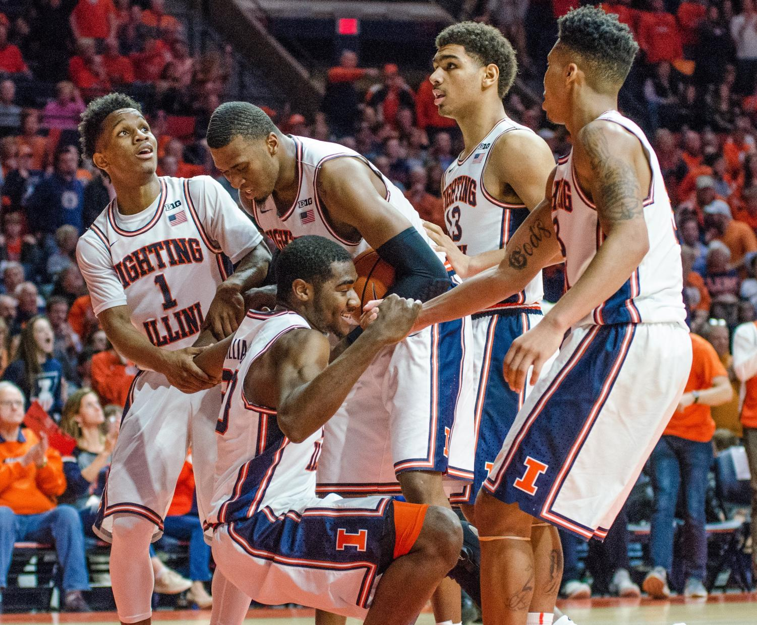 Trent Frazier, Leron Black and Te'Jon Lucas help up teammate Da'Monte Williams during Illinois' 86-93 loss to No. 6 Purdue on Feb. 22.