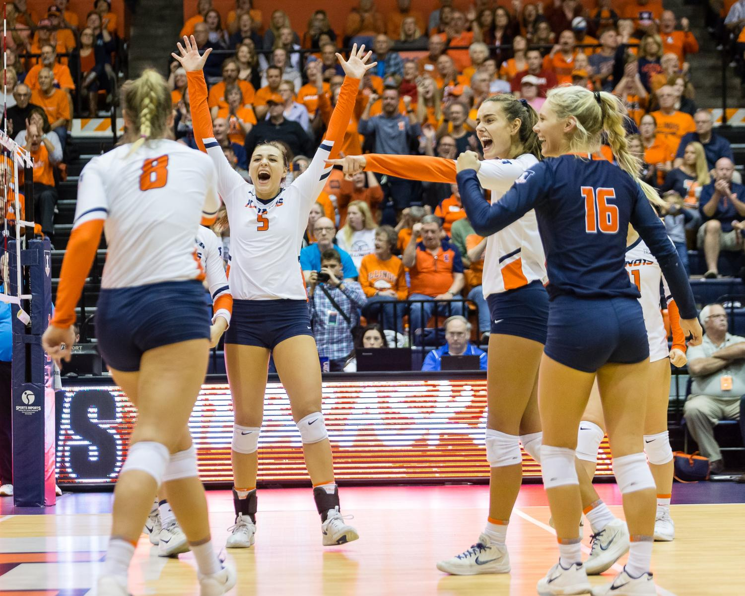 Illinois middle blocker Ali Bastianelli (5), outside hitter Jacqueline Quade (7) and defensive specialist Megan O'Brien (16) celebrate after outside hitter Beth Prince (8) scored a kill during the match against Nebraska at Huff Hall in on Sept. 29, 2018. The Illini lost 3-1.