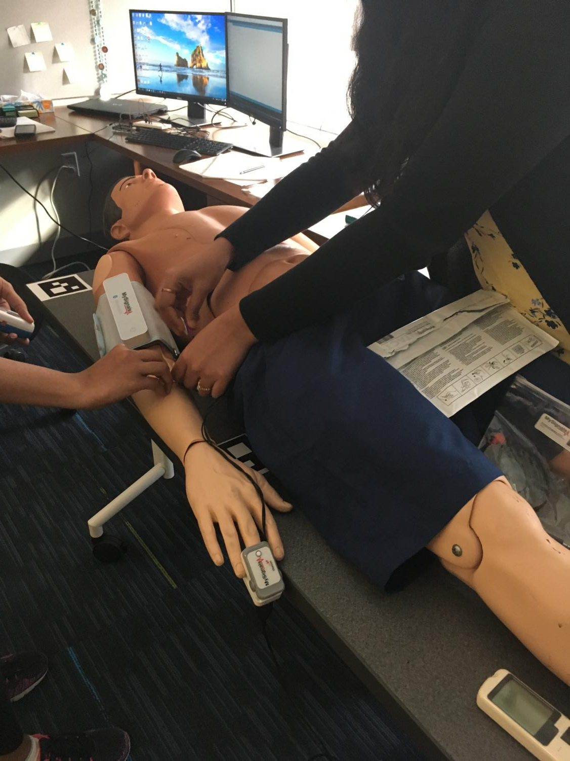 Lab engineers in the Health Care Engineering Systems Center demonstrate sensors that measure patients' vitals (blood sugar, heart rate, etc) and connect ongoing data to an iCloud system that can be shared with the patients' doctor on a dummy/mannequin.