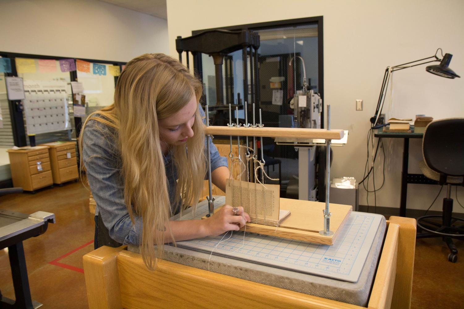 Anneka Vetter rebinds an old book before its eventual encasement in Fresh Press Studio's case paper at the Oak Street Library on Friday. The studio is working to create sustainable paper.