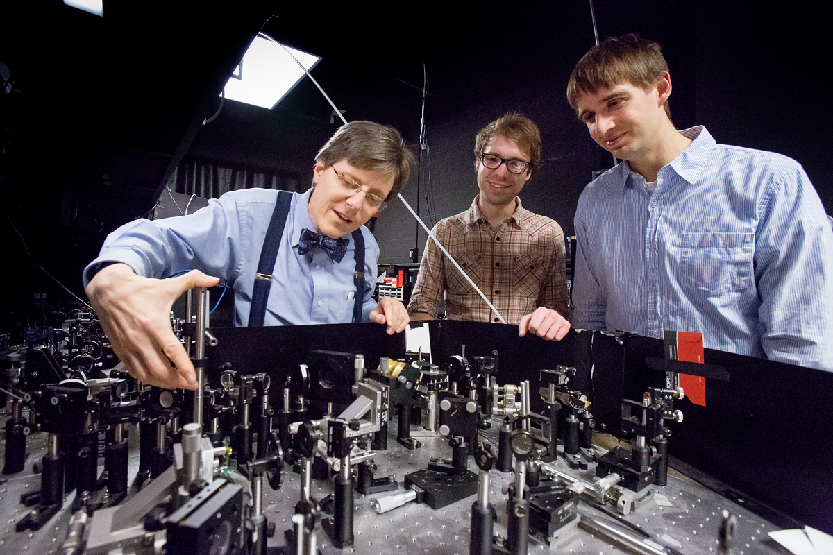 Physics Professor Paul Kwiat (left) working with graduate students in the lab at Loomis Laboratory of Physics. Kwiat is working on improving quantum computing.