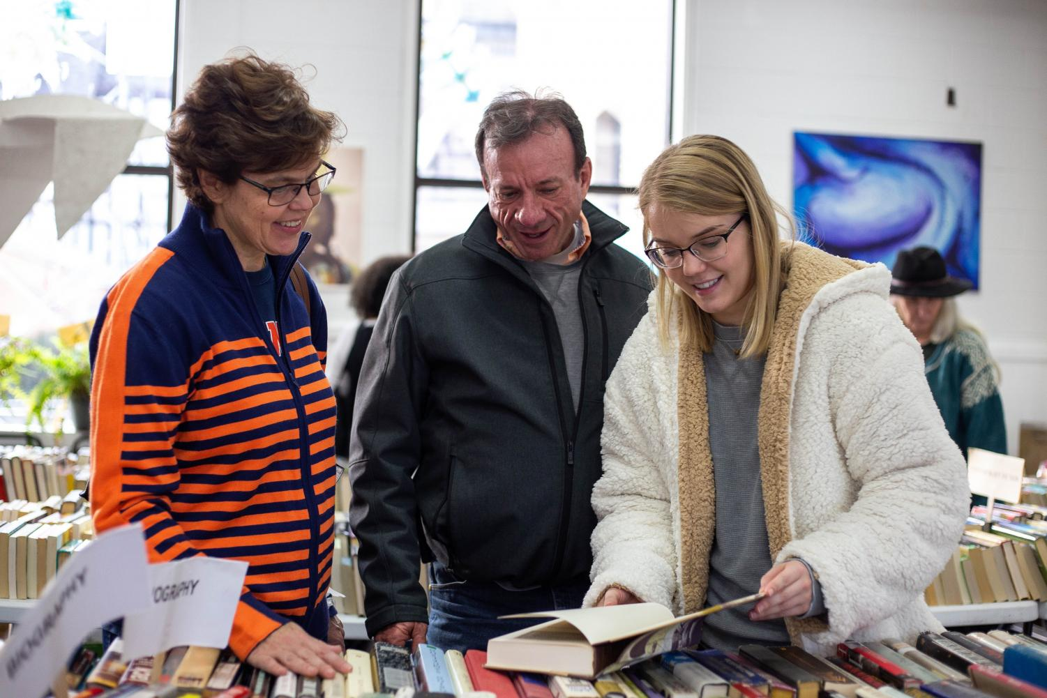 Madeleine Brown, president of the Books to Prisoners RSO, helps Renee and Neal Brown find books at the group's book sale at the Independent Media Center on Nov. 3. The RSO, which started as a local nonprofit organization, aims to provide incarcerated individuals with access to reading material.