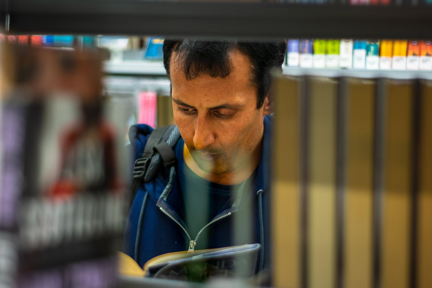 Hezbullah Akmal skims fiction novels at the Champaign Public Library on Monday. Akmal, an immigrant from Afghanistan, came to Champaign-Urbana last year when he was being threatened after working with the American government.