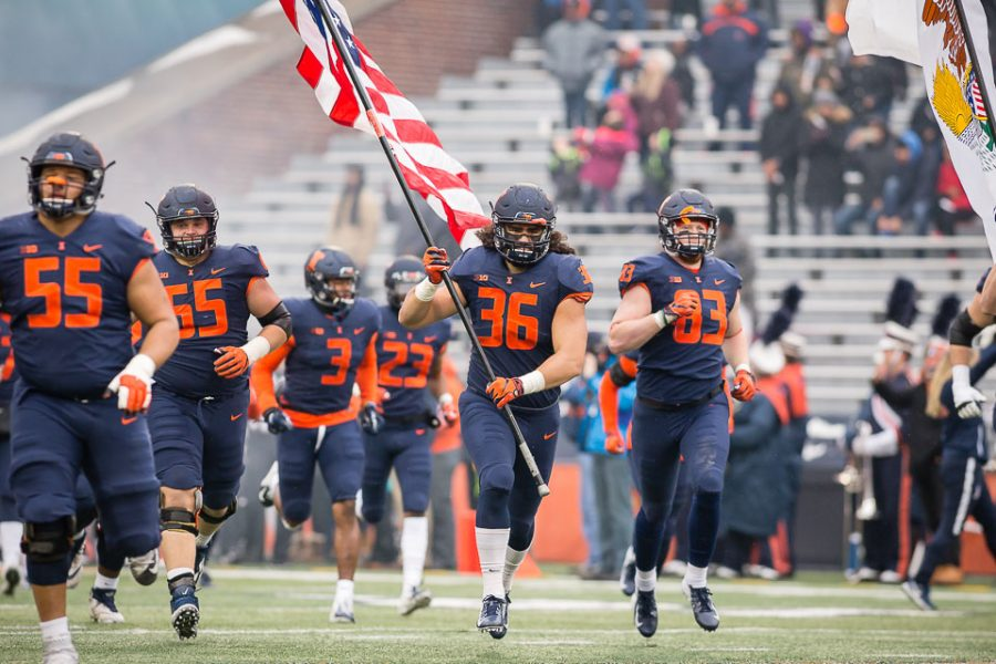 Illinois+tight+end+Austin+Roberts+%2836%29+carries+the+American+flag+onto+the+field+before+the+game+against+Iowa+at+Memorial+Stadium+on+Saturday%2C+Nov.+17%2C+2018.