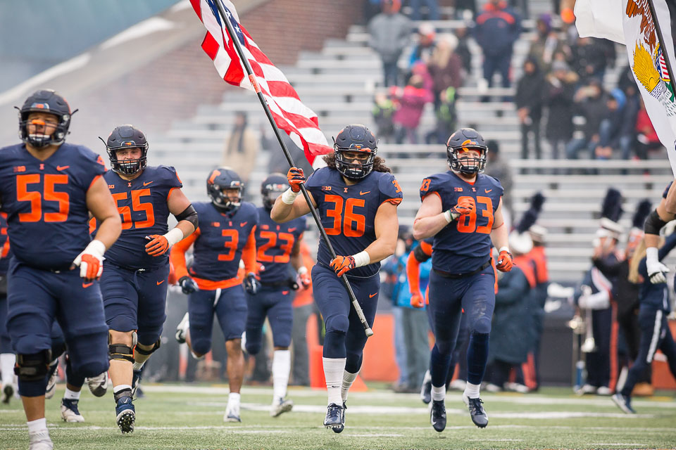Illinois tight end Austin Roberts (36) carries the American flag onto the field before the game against Iowa at Memorial Stadium on Saturday, Nov. 17, 2018.