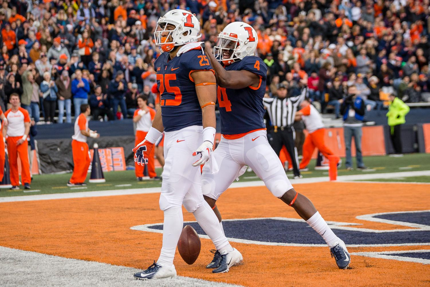 Illinois running back Dre Brown (left) celebrates with wide receiver Ricky Smalling (right) after scoring a touchdown during the game against Minnesota at Memorial Stadium on Saturday. The Illini won 55-31. Brown ran for a career-high 92 yards on the day and scored his first collegiate touchdown.