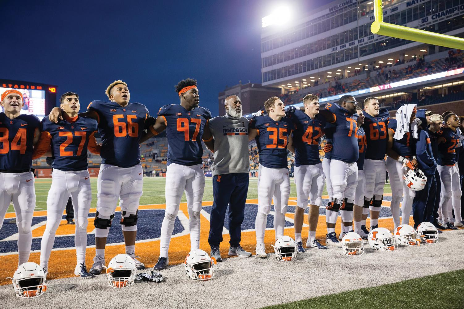 """Illinois head coach Lovie Smith sings """"Hail to the Orange"""" with his team after the game against Minnesota at Memorial Stadium on Saturday. The Illini won 55-31."""