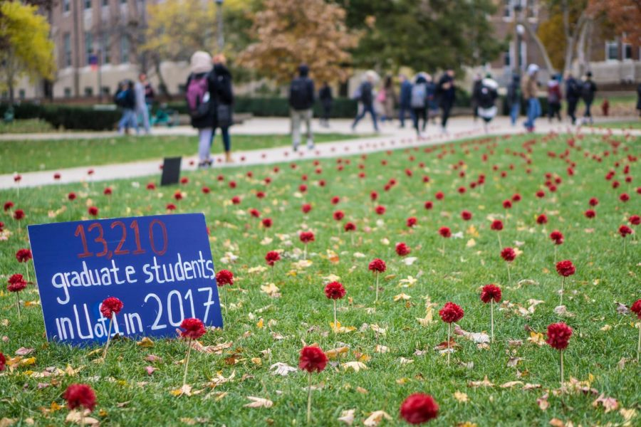 Carnations and signs set up by Amnesty International line the Main Quad to raise awareness for gun violence on Thursday. This sign compares the number of graduate students enrolled at the University to those affected by gun violence in the United States.