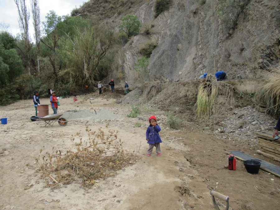 A+project+worksite+in+Bolivia+attracts+community+laborers+who+often+bring+their+children%2C+pets%2C+and+elderly+relatives.+While+student+workers+wearing+hardhats+work+on+an+irrigation+trench%2C+a+toddler+meanders+among+workers+who+use+local+methods+for+mixing+concrete+with+shovel+and+pail+%E2%80%93+a+practice+that+violates+multiple+workplace+safety+procedures+practiced+in+the+industrialized+world.