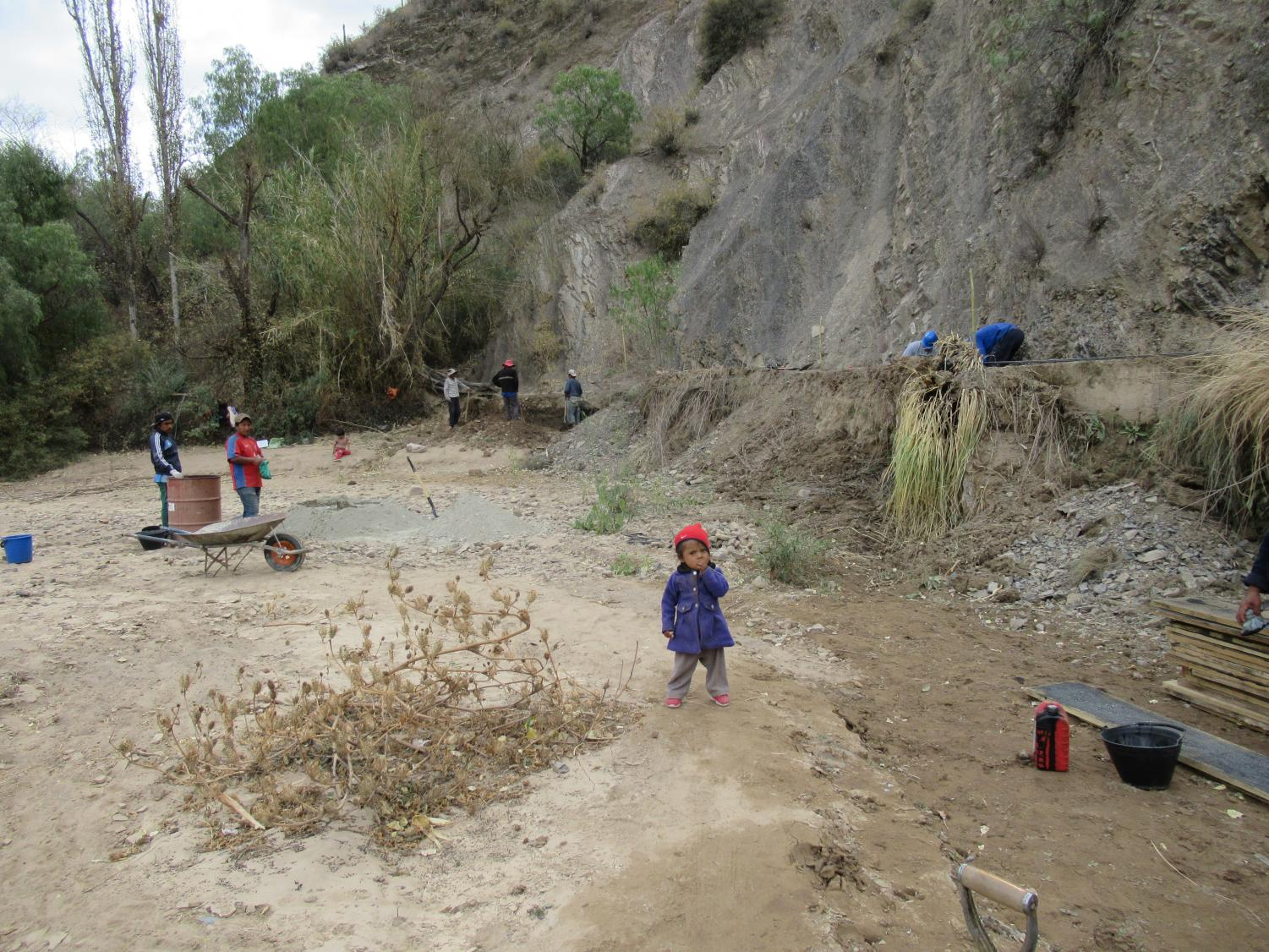 A project worksite in Bolivia attracts community laborers who often bring their children, pets, and elderly relatives. While student workers wearing hardhats work on an irrigation trench, a toddler meanders among workers who use local methods for mixing concrete with shovel and pail – a practice that violates multiple workplace safety procedures practiced in the industrialized world.