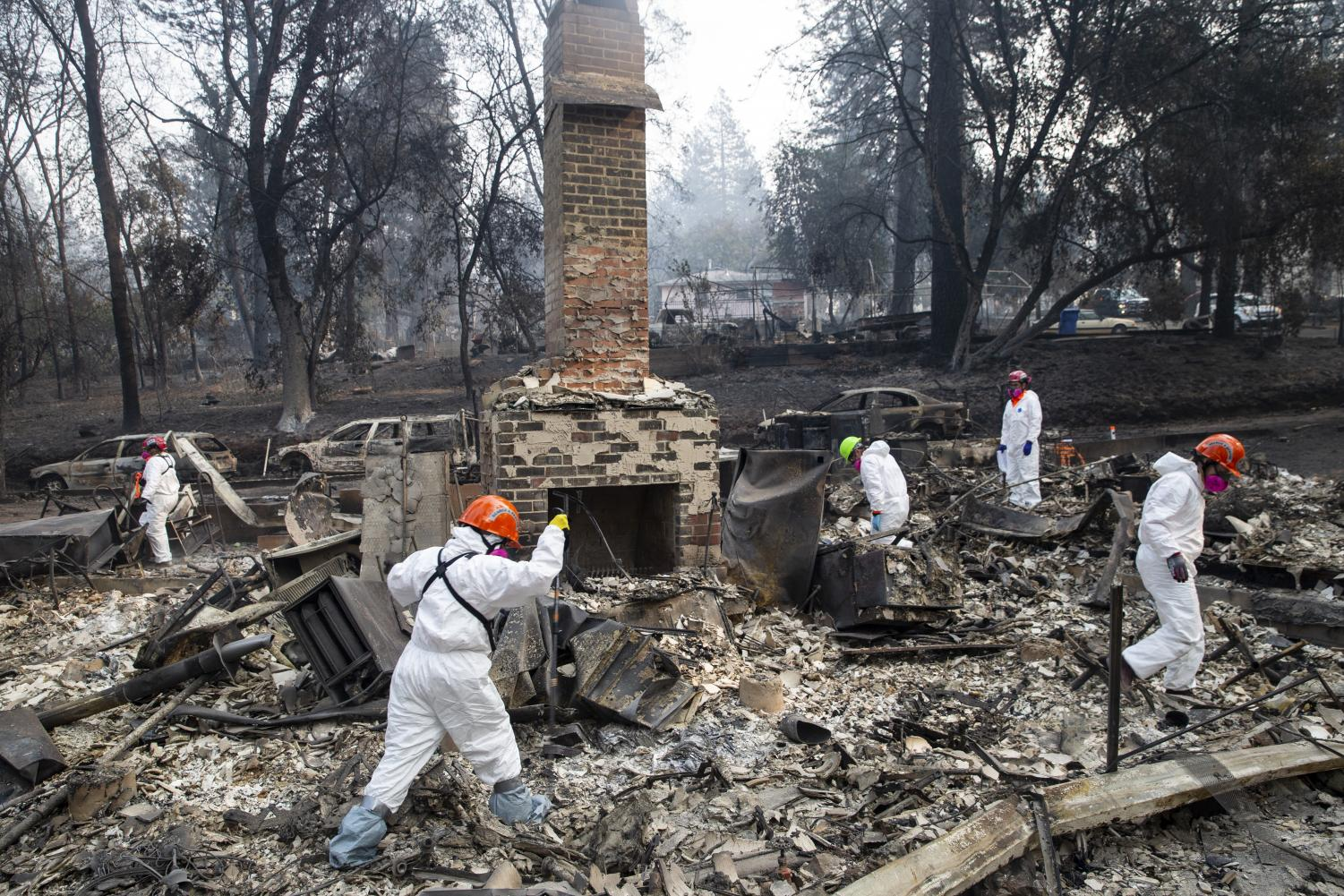 Search and rescue teams inspect the grounds of a house burned down by the Camp Fire along Boquest Boulevard on Nov. 17 in Paradise, California. University students from the area stay updated from afar as their family and friends recover.