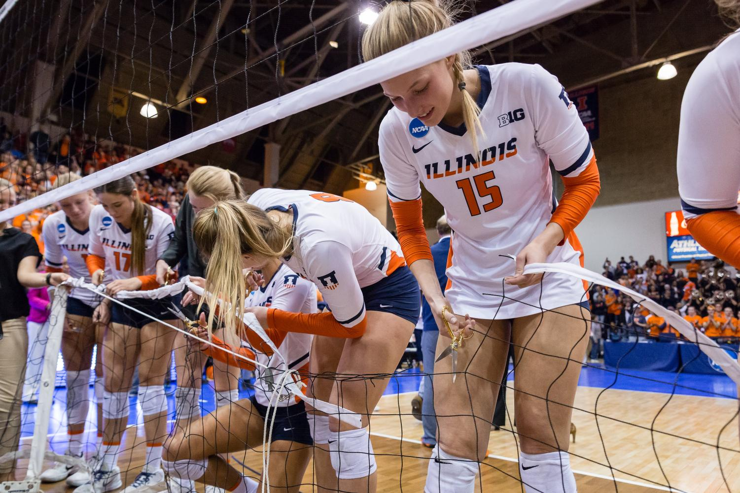 Illinois outside hitter Megan Cooney (15) and outside hitter Beth Prince (8) cut the net after the match against Wisconsin Saturday. The Illini will participate in the Final Four in Minneapolis, Minnesota, this week.