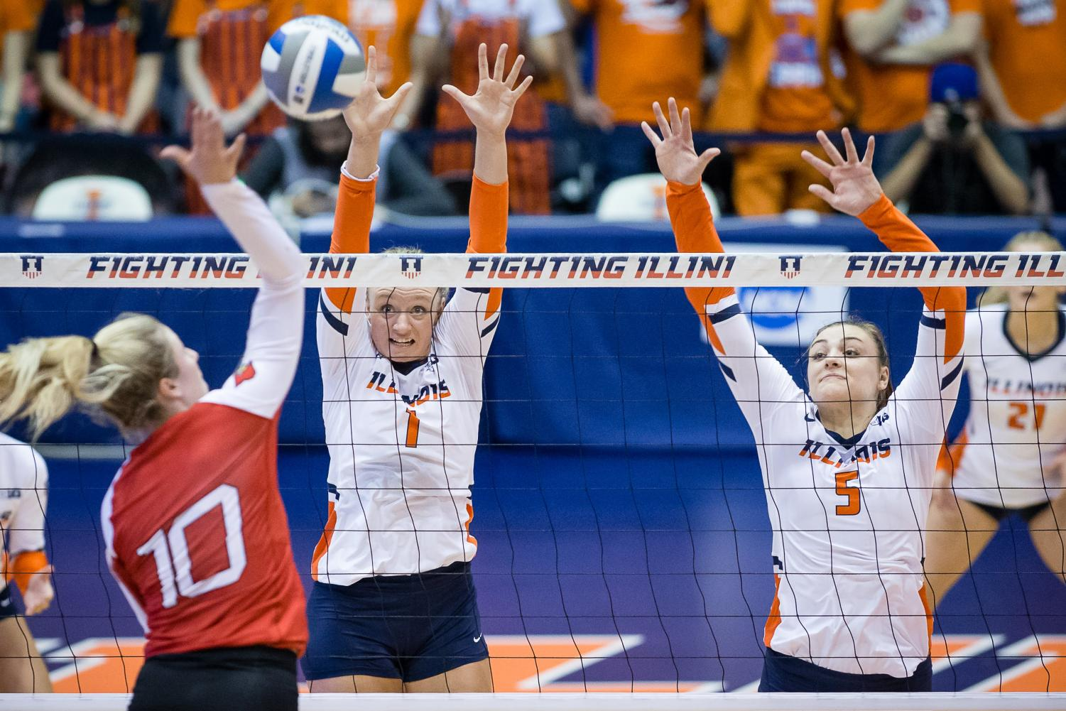 Illinois setter Jordyn Poulter, left, and middle blocker Ali Bastianelli, right, try to block the ball during the match against Louisville in the second round of the NCAA Tournament at Huff Hall on Saturday. The Illini won 3-1.